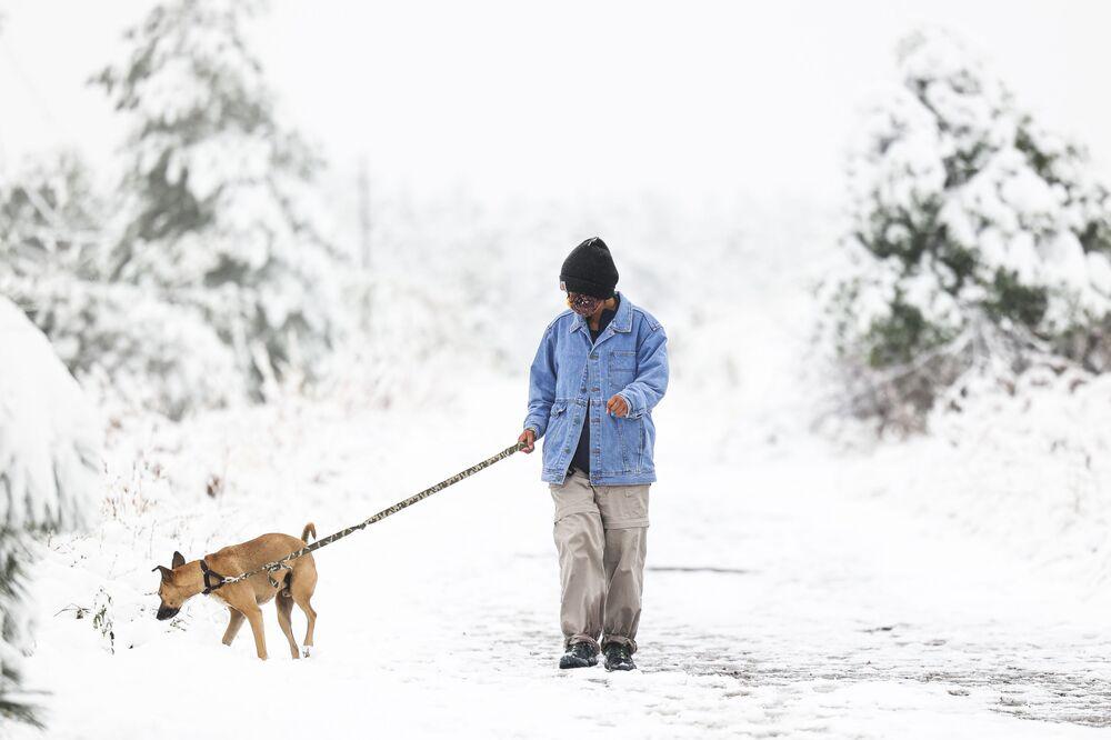 Una donna passeggia con il suo cane dopo una nevicata in Colorado.
