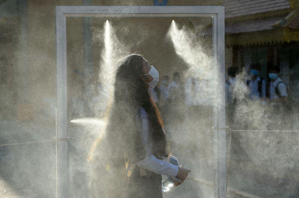 Una studente passa attraverso un cancello con lo spray disinfettante in Cambogia.