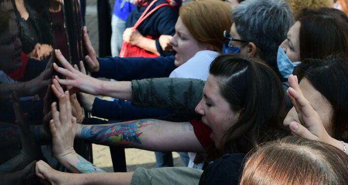 Donne spingono il veicolo della polizia al corteo femminile a Minsk