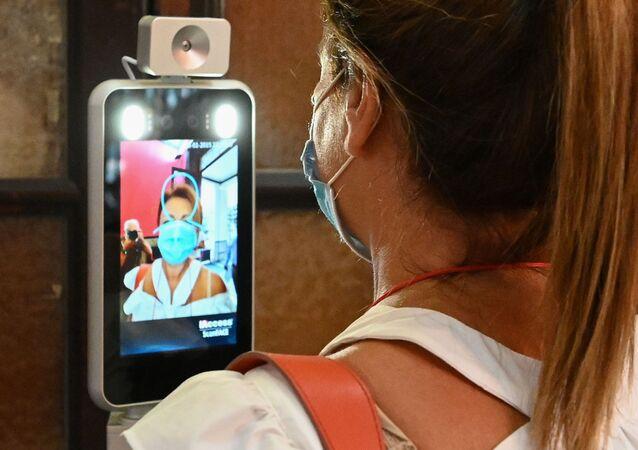 Un'insegnante misura la temperatura prima di entrare in una scuola di Roma