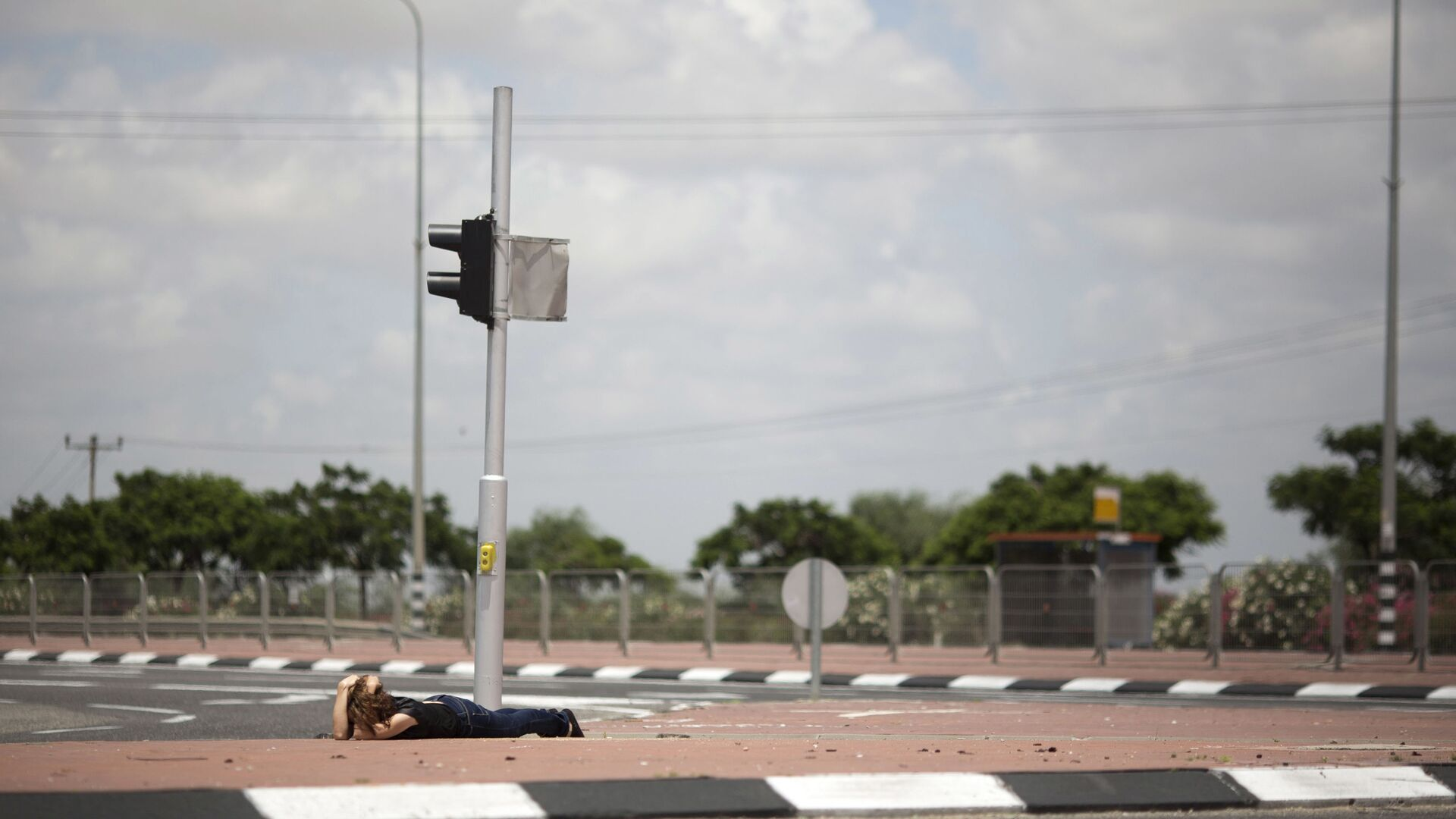 An Israeli woman takes cover as siren alarming sounds warning of rocket attacks by Palestinians militants from Gaza Strip in Ashkelon, southern Israel, Monday, July 14, 2014. - Sputnik Italia, 1920, 11.05.2021