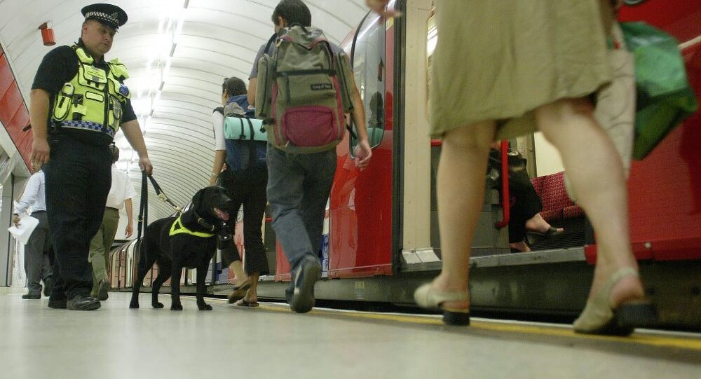 Counter Terrorism Police Dog, officer Vinni, sniffs for explosives as he patrols Liverpool Street underground platform as passengers alight from a tube train, Wednesday July 20, 2005, as security is stepped up at Liverpool Street Tube Station in London.