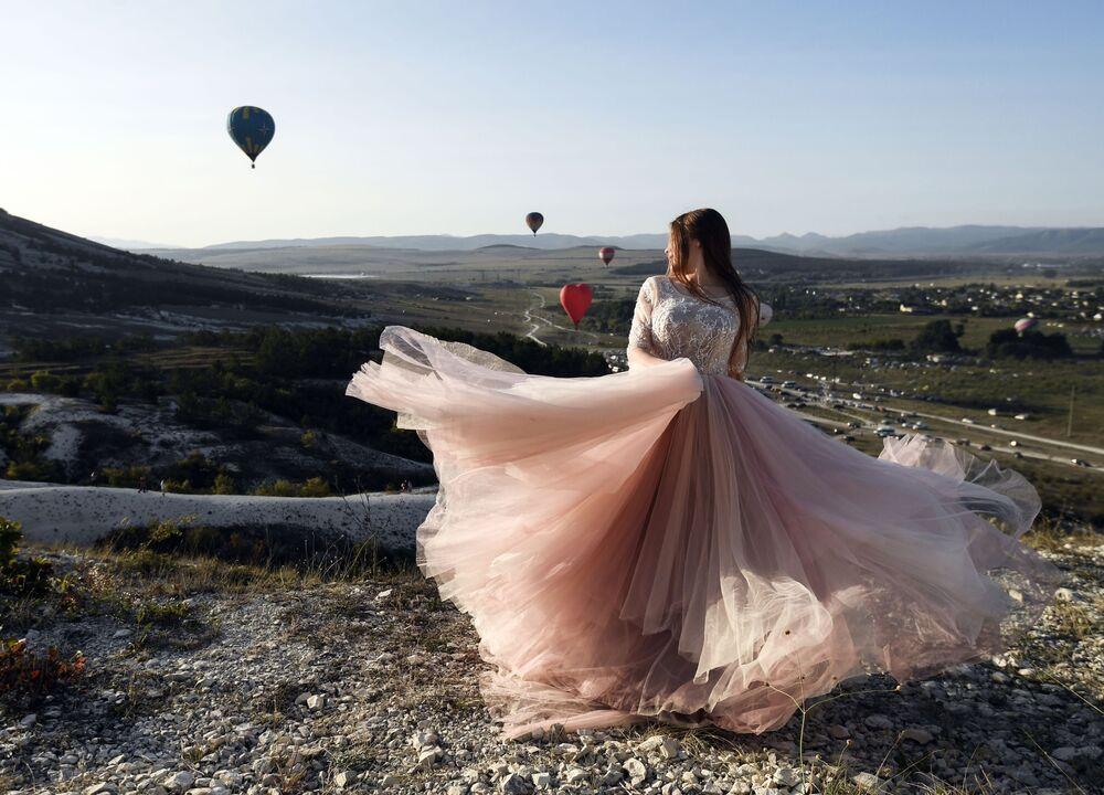 Una ragazza durante il festival di aeronautica vicino sullo sfondo della roccia bianca nella regione di Belogorsk della Repubblica di Crimea