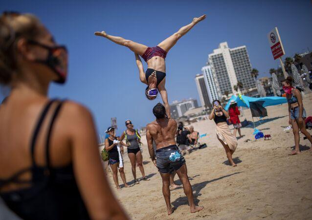 Acrobati in maschera sulla spiaggia di Tel Aviv