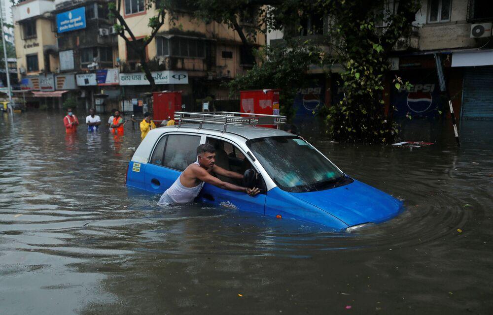 Un uomo spinge un taxi lungo una strada inondata dopo un temporale a Mumbai, in India