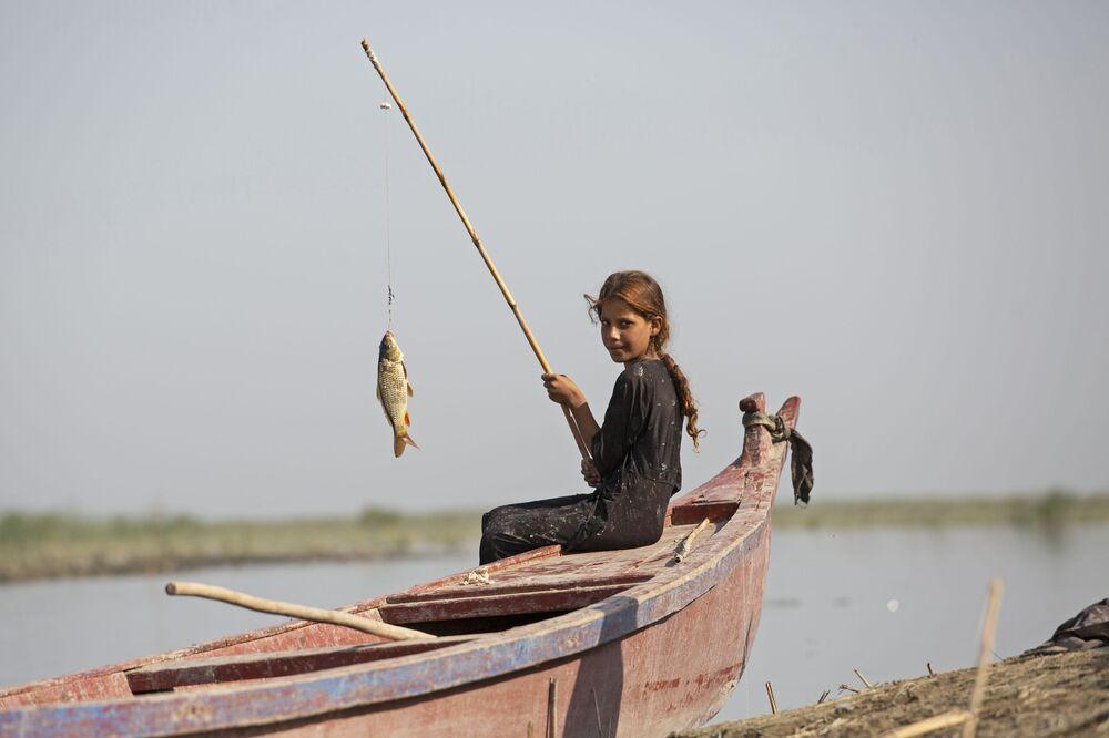 Una ragazza sta pescando vicino alla città Basra, Iraq