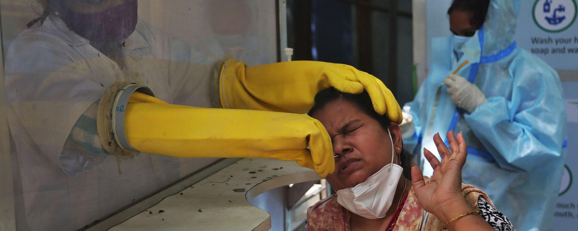 Медицинский работник проводит тест в Индии - Sputnik Italia, 1920, 24.03.2021