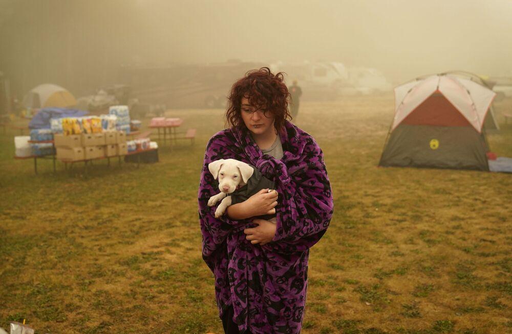 Una donna tiene il suo cane avvolto in una coperta in un centro di evacuazione dagli incendi forestali a Oak Grove, Oregon