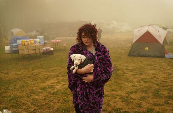 Una donna tiene il suo cane avvolto in una coperta in un centro di evacuazione dagli incendi forestali a Oak Grove, Oregon - Sputnik Italia