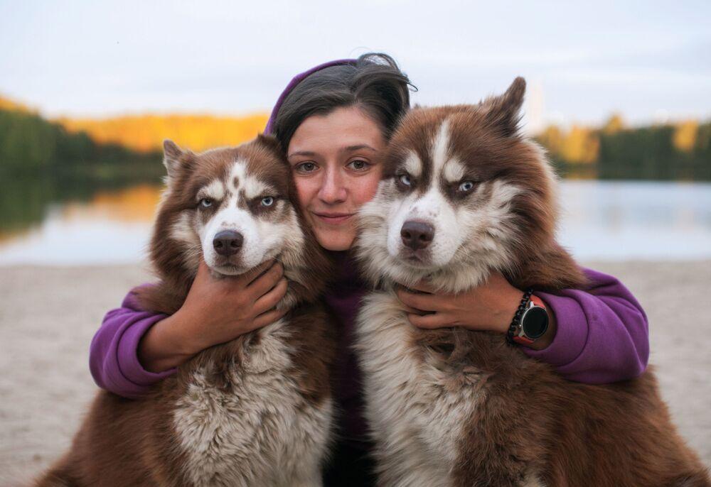 Una partecipante della gara dei cani da tiro nella regione di Tyumen, Russia, con i suoi cani husky
