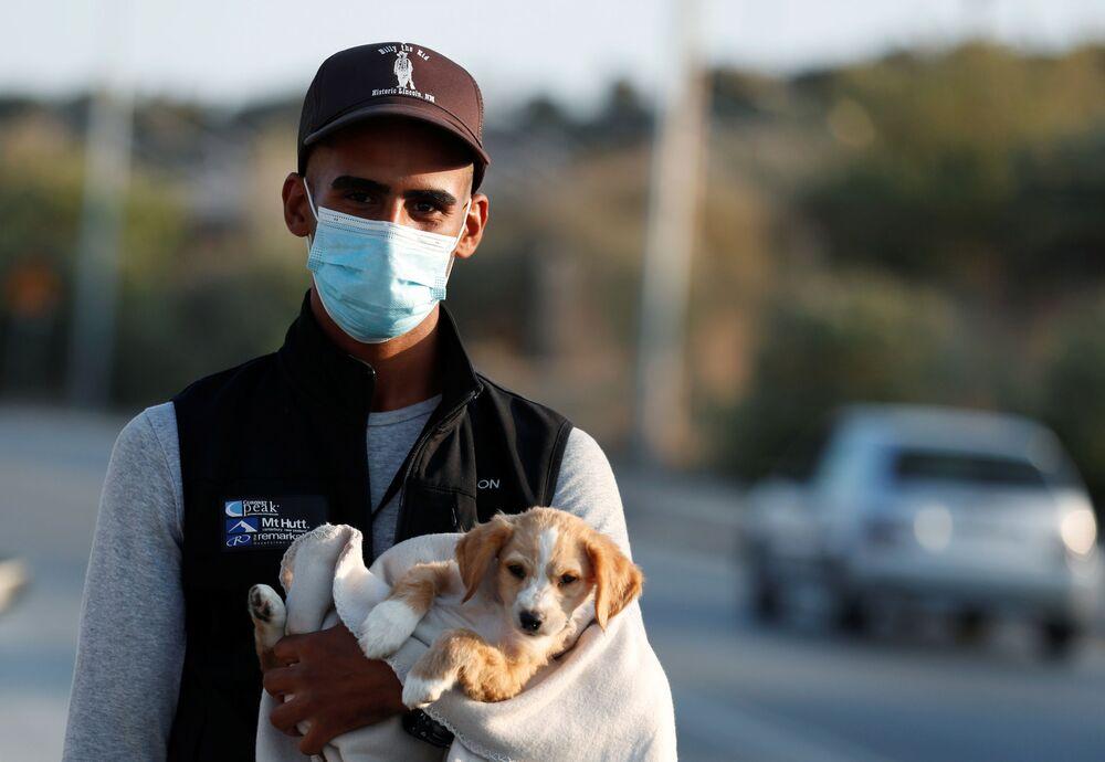 Un profugo porta un cane durante il trasferimento in un nuovo campo temporaneo per migranti e rifugiati sull'isola di Lesbo, in Grecia