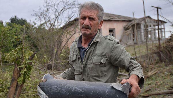 Un uomo tiene un frammento di munizione  dopo che le truppe azere hanno bombardato la città di Martuni in Karabakh - Sputnik Italia