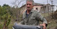 Un uomo tiene un frammento di munizione  dopo che le truppe azere hanno bombardato la città di Martuni in Karabakh