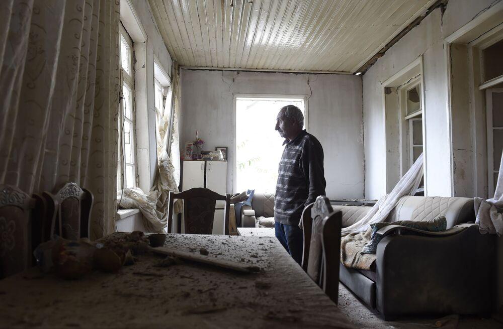 Un residente mostra una camera della casa bombardata a Martuni