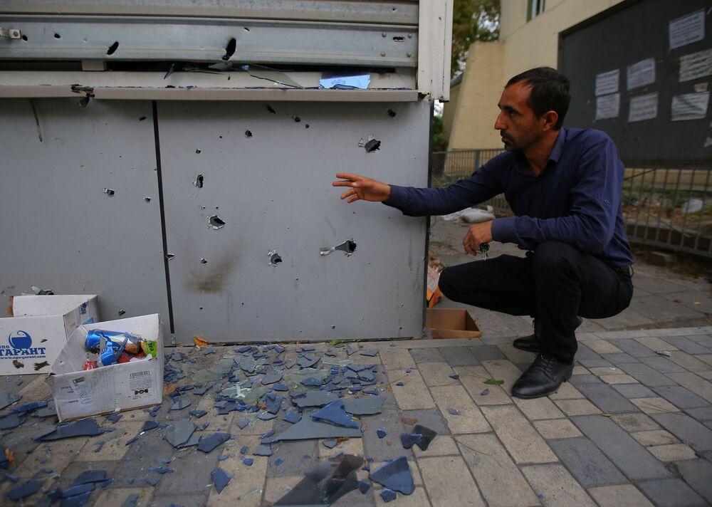 Un uomo fa vedere le distruzioni dopo i bombardamenti nella città Terter