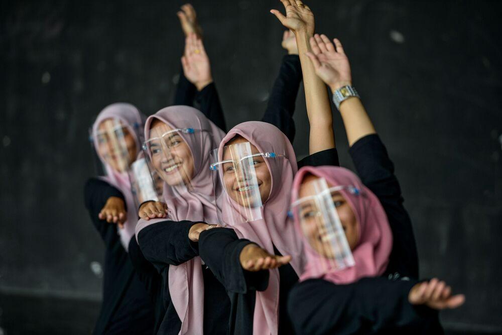 I ballerini che indossano visiere protettive contro il coronavirus si esibiscono durante una sessione di prove presso un centro artistico e culturale a Banda Aceh, il 26 settembre 2020