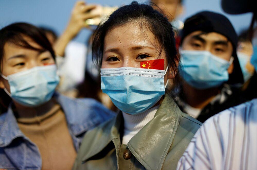 Le persone che indossano mascherine facciali, in seguito allo scoppio della malattia del coronavirus (COVID-19), partecipano a una cerimonia di alzabandiera in piazza Tiananmen per celebrare il 71° anniversario della fondazione della Repubblica popolare cinese a Pechino, Cina