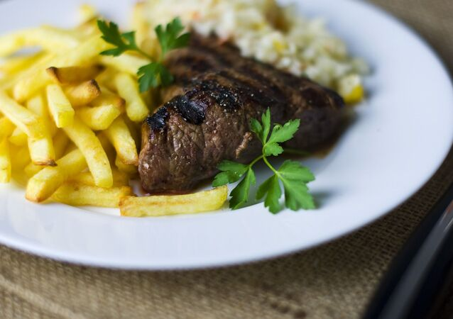 Un plato con carne y papas