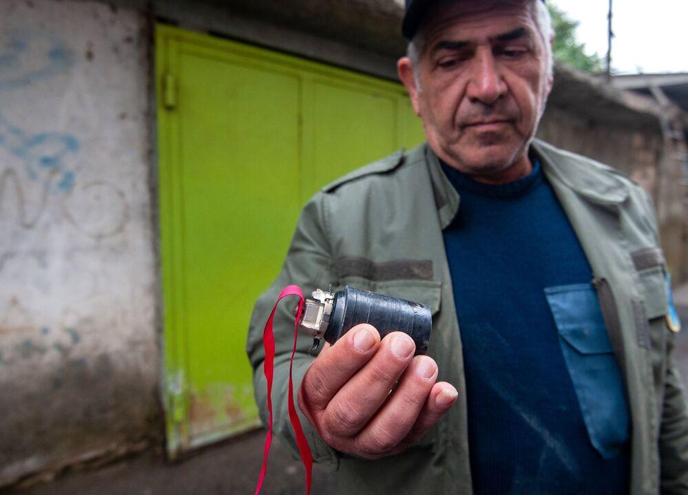 Un uomo tiene in mano una munizione a grappolo trovata dopo il bombardamento notturno di Stepanakert