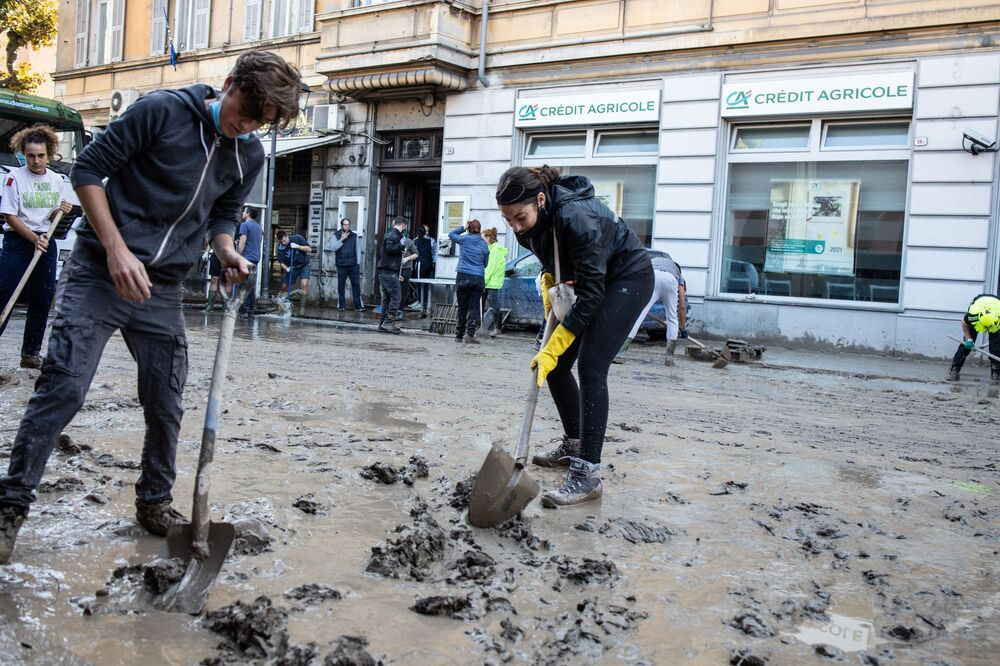 I residenti della città italiana Ventimiglia puliscono le strade dal fango dopo l'alluvione