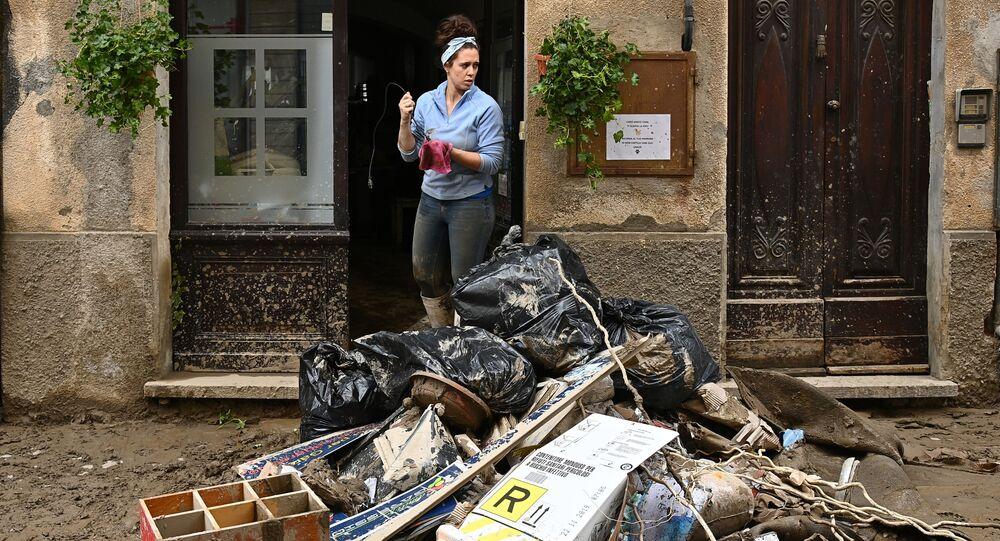 Una donna pulisce la sua casa dopo una frana a Garessio, Piemonte