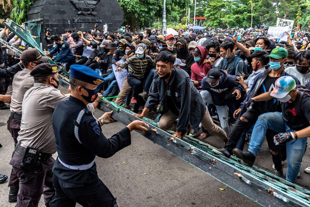 I manifestanti si scontrano con gli agenti di polizia a seguito di una protesta contro le riforme di lavoro del governo fuori dall'edificio dell'Assemblea regionale del popolo a Semarang, provincia di Java centrale, Indonesia, il 7 ottobre 2020