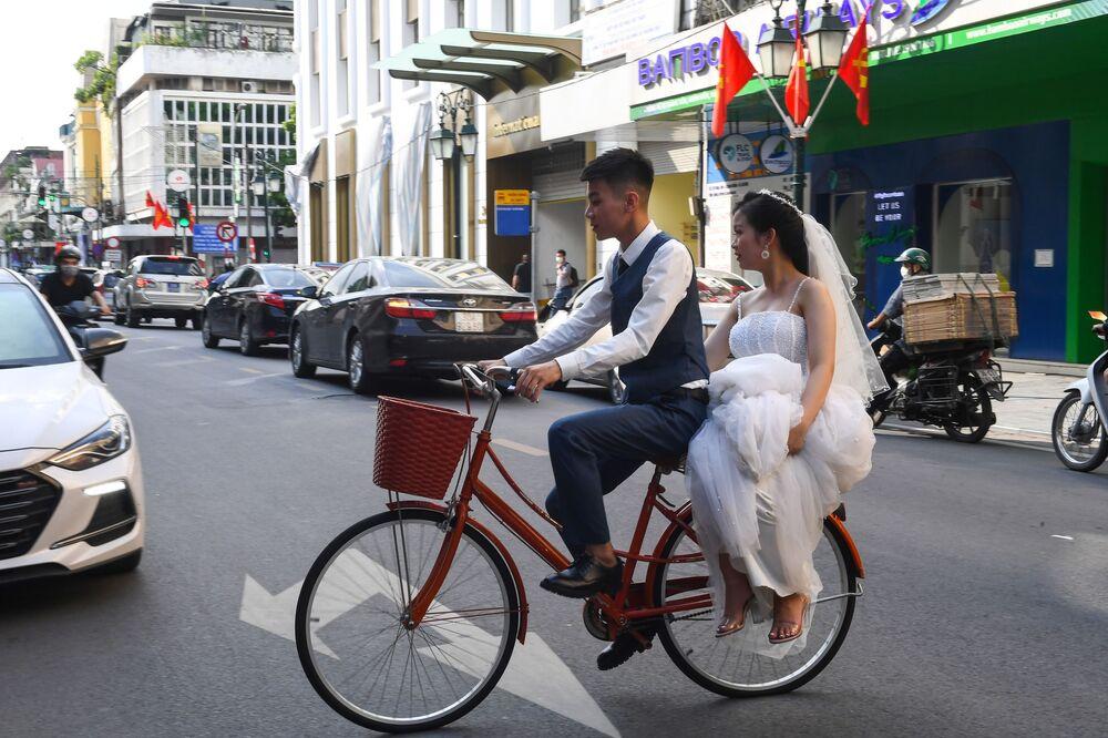 Gli sposi in bicicletta in una strada ad Hanoi il 2 ottobre 2020