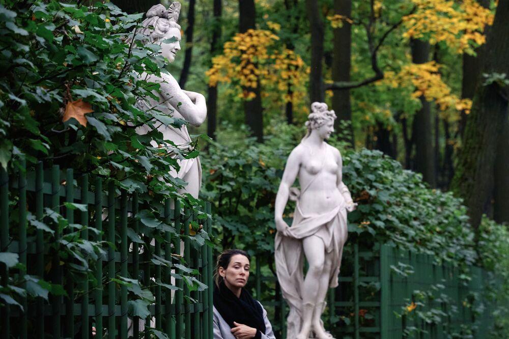 Una visitatrice vicino alle sculture nel Giardino d'Estate a San Pietroburgo, Russia