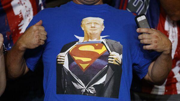Un sostenitore del presidente Donald Trump indossa una maglietta con l'immagine del presidente nei panni di Superman durante un raduno elettorale alla Williams Arena di Greenville, N.C., mercoledì 17 luglio 2019. - Sputnik Italia