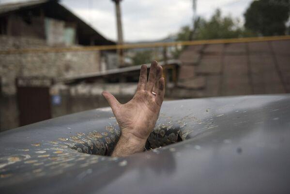 Un buco nel tetto di un'auto causato dal bombardamento di Stepanakert nel Nagorno-Karabakh - Sputnik Italia