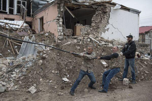 Uomini durante la ricostruzione delle reti elettriche danneggiate dal bombardamento di Stepanakert nel Nagorno-Karabakh - Sputnik Italia