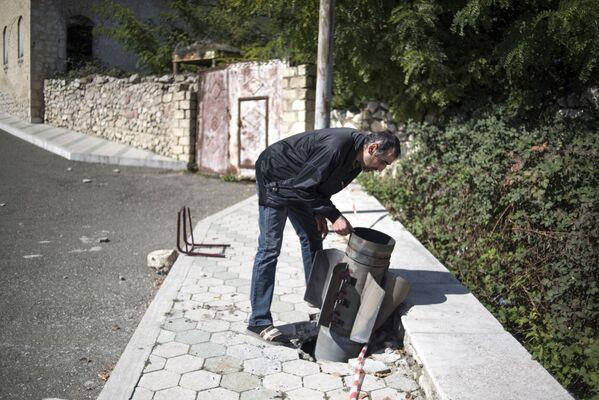 Un residente locale vicino ad una granata inesplosa sulla strada di Martuni - Sputnik Italia