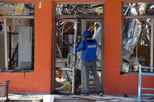 Un rappresentante dei mass media davanti a un negozio a Martakert distrutto dai bombardamenti - Sputnik Italia