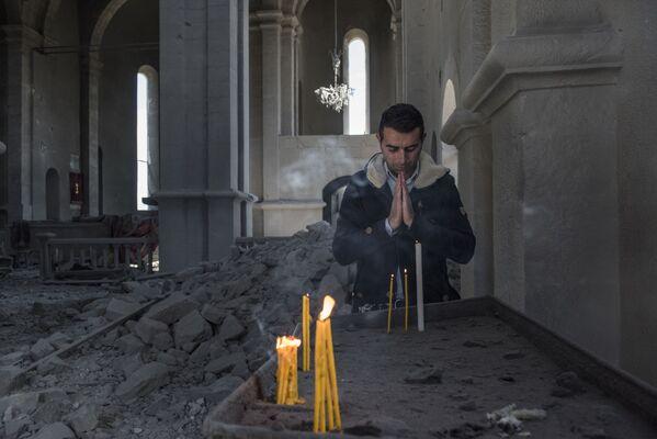 Un residente locale in una chiesa distrutta dai bombardamenti nella città di Shushi - Sputnik Italia