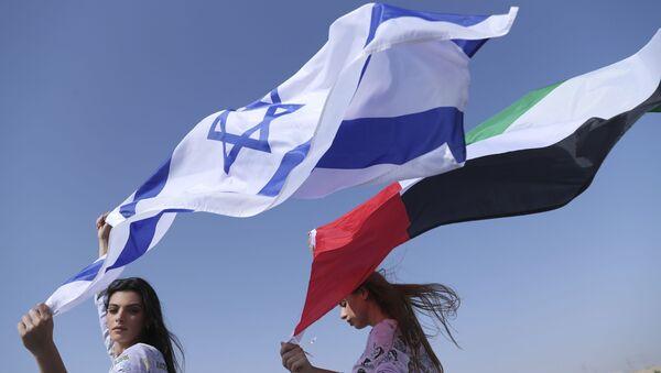 La modella israeliana May Tager, a sinistra, tiene la bandiera blu e bianca di Israele con la Stella di David mentre accanto a lei Anastasia Bandarenka, una modella di Dubai originaria della Russia, sventola la bandiera degli Emirati, durante un servizio fotografico a Dubai, Emirati Arabi Uniti Emirates, domenica 8 settembre 2020 - Sputnik Italia