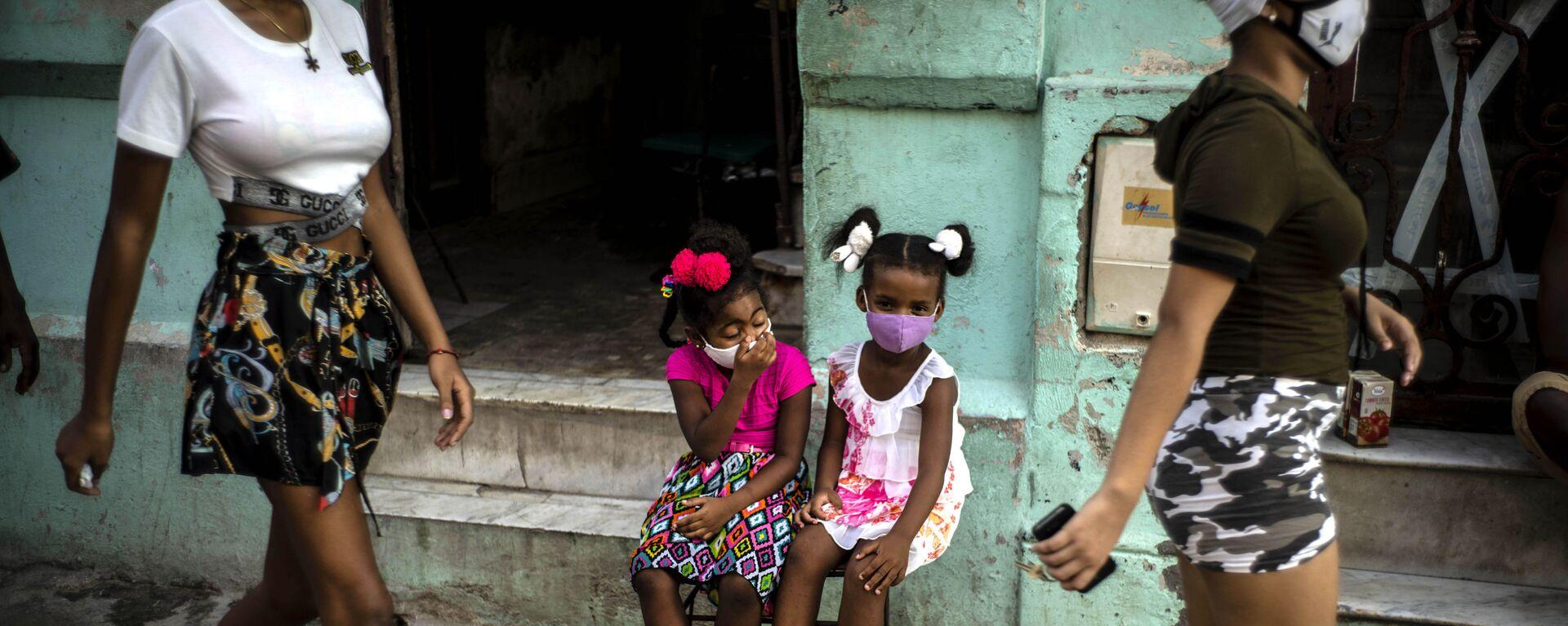 Девочки в масках ждут своих родителей, сидя на стуле в Гаване, Куба - Sputnik Italia, 1920, 12.07.2021