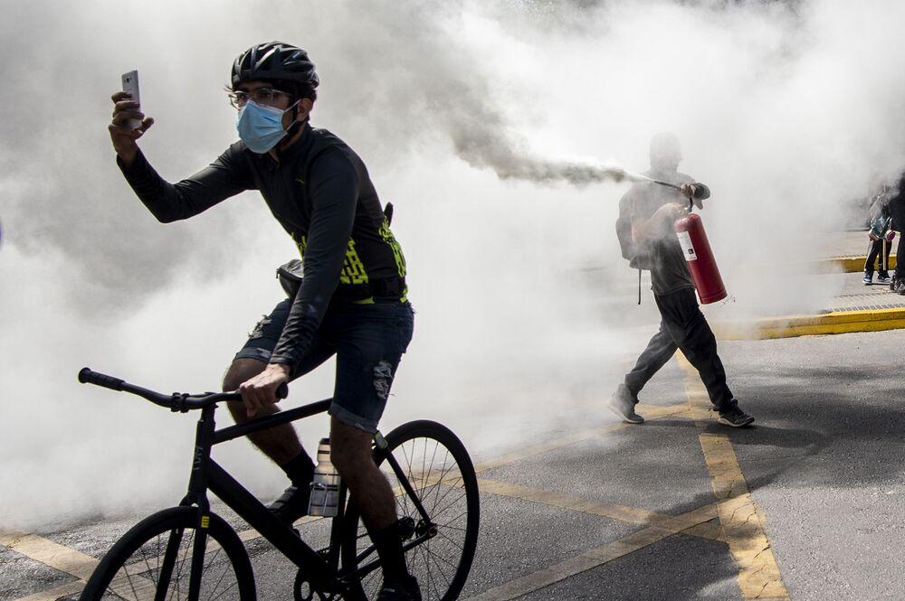 I manifestanti durante gli scontri con la polizia antisommossa durante una protesta nel centro di Santiago, il 12 ottobre 2020