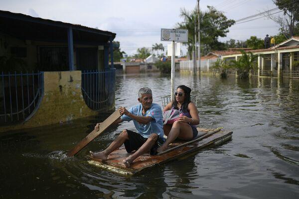 I residenti di Maracay usano una porta come zattera, Venezuela.  - Sputnik Italia