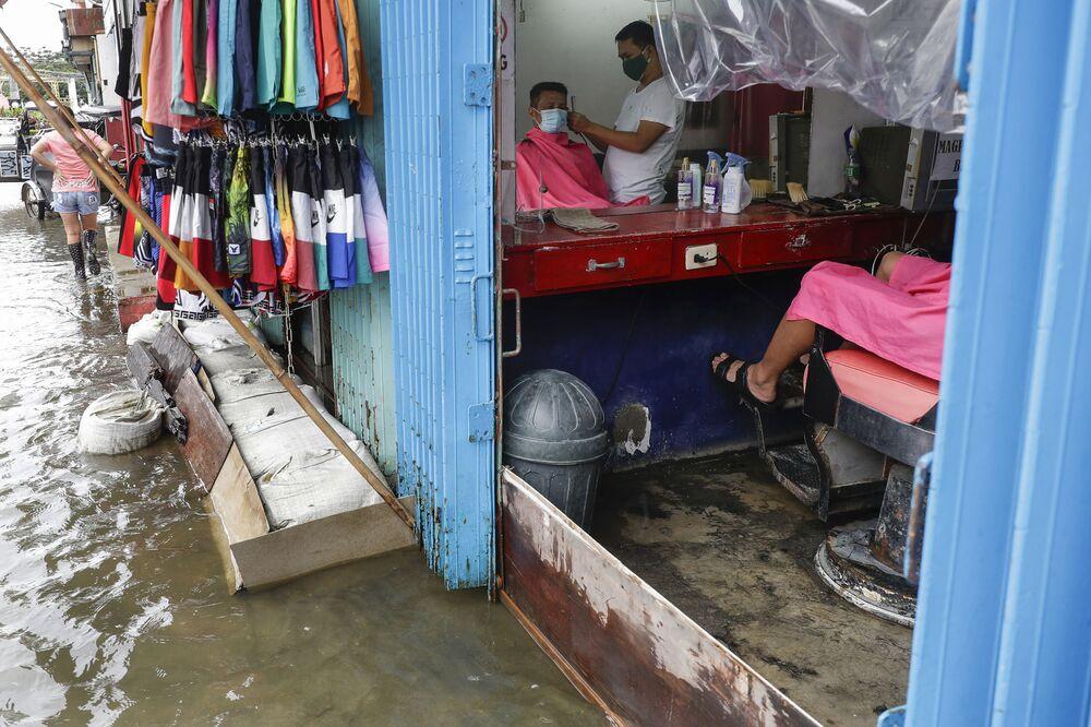 Un uomo dal barbiere in una strada inondata dopo la tempesta tropicale Molave che ha colpito le Filippine.