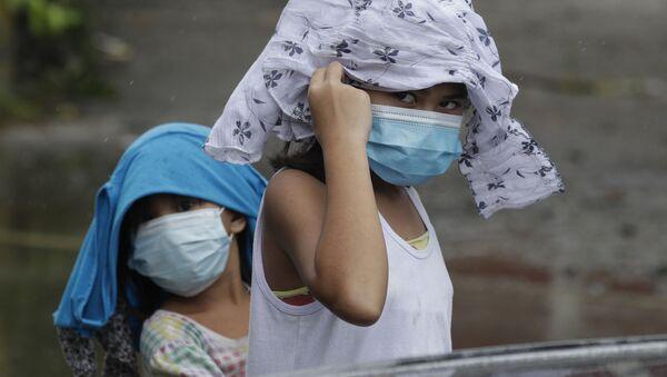 Девочки в медицинских масках пытаются укрыться от дождя на Филиппинах  - Sputnik Italia