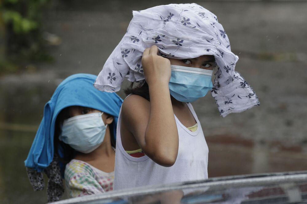 Ragazzine in mascherina cercano di coprirsi dalla pioggia, Filippine.