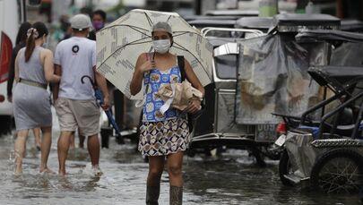 Una donna in una strada inondata dopo la tempesta tropicale Molave, provincia di Pampanga, nel nord delle Filippine, lunedì 26 ottobre 2020.