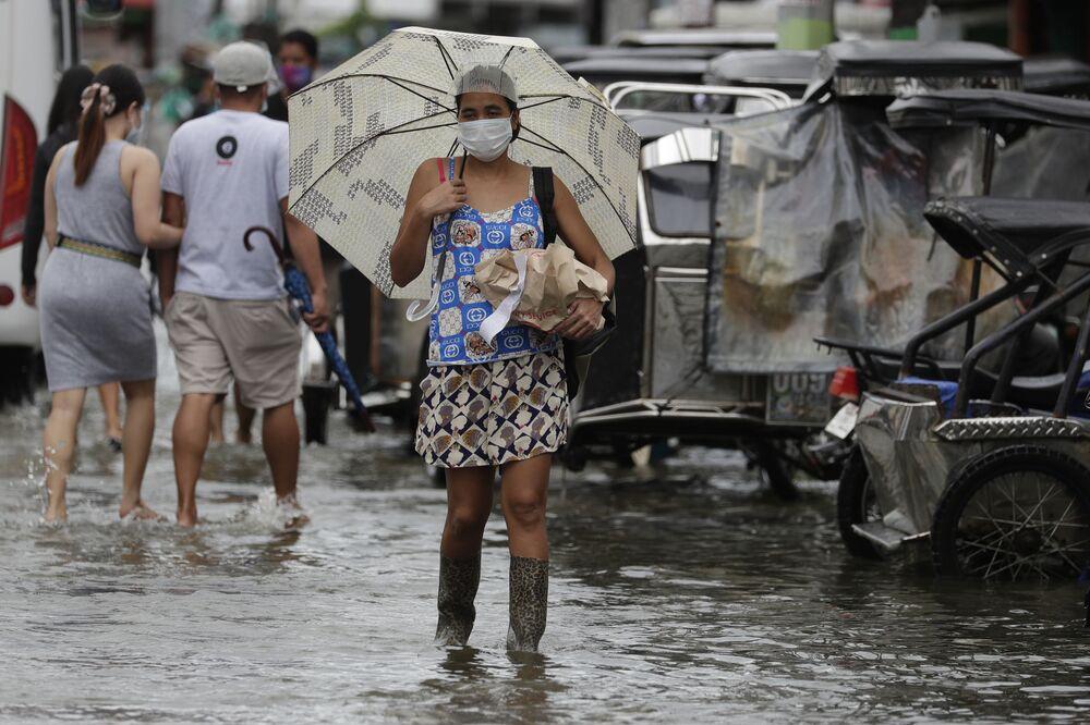 Una donna in una strada inondata dopo la tempesta tropicale Molave, Filippine.