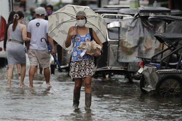 Una donna in una strada inondata dopo la tempesta tropicale Molave, Filippine.  - Sputnik Italia