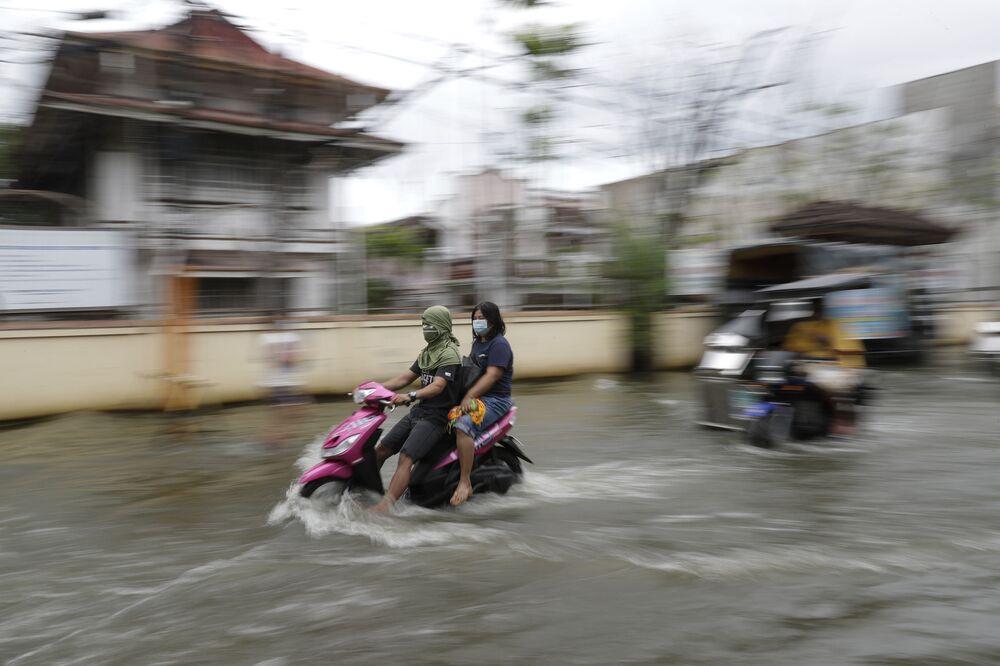 Persone in mascherina in una strada inondata dopo la tempesta tropicale Molave, Filippine.