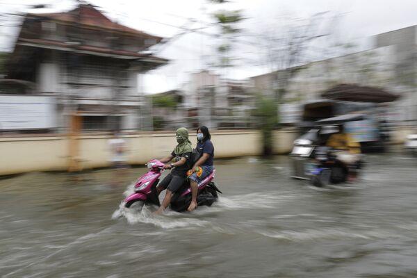 Persone in mascherina in una strada inondata dopo la tempesta tropicale Molave, Filippine. - Sputnik Italia