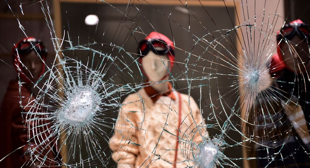 A damaged window of a store is seen as people protest against the new restrictions introduced by the government to curb the coronavirus disease (COVID-19) infections, in Turin, Italy, October 26, 2020.