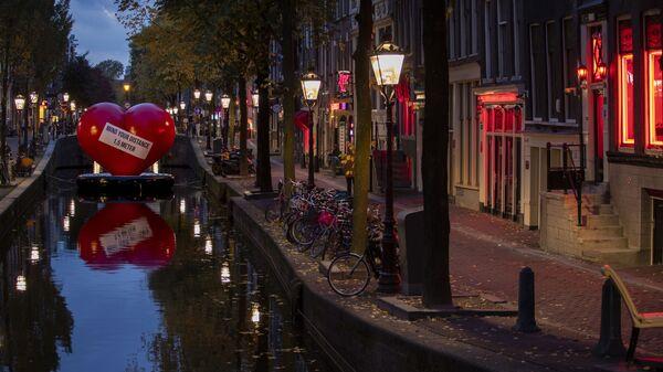 Красное сердце с напоминанием соблюдать социальную дистанцию в почти пустом квартале красных фонарей в Амстердаме, Нидерланды - Sputnik Italia
