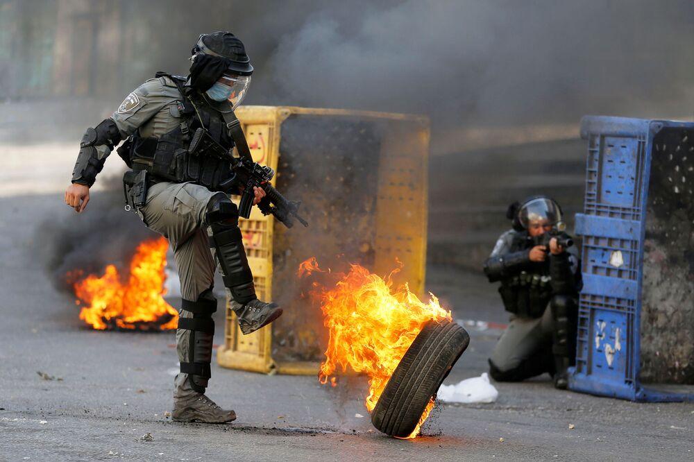 Un agente di polizia israeliano calcia un pneumatico in fiamme nel corso della protesta anti-israeliana a Hebron, in Cisgiordania, 23 ottobre 2020.
