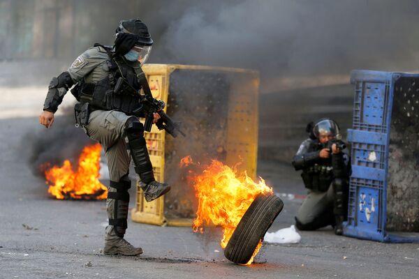 Un agente di polizia israeliano calcia un pneumatico in fiamme nel corso della protesta anti-israeliana a Hebron, in Cisgiordania, 23 ottobre 2020.  - Sputnik Italia